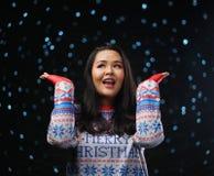 亚裔女孩佩带的圣诞节毛线衣黑暗的焕发雪背景 图库摄影