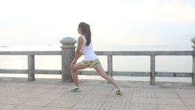 亚裔女孩做在堤防的锻炼在黎明 影视素材