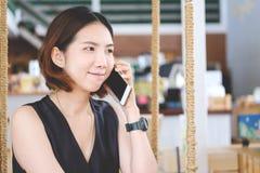亚裔女孩听在她的手机的一个电话的,年轻beauti 库存照片