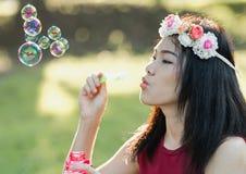 亚裔女孩吹的肥皂泡 免版税库存照片