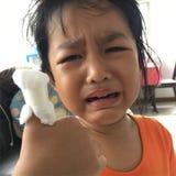 亚裔女孩哄骗哭泣与在手指的绷带 库存图片