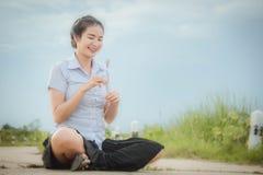 亚裔女孩在草甸和看的路微笑着 免版税图库摄影