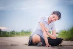 亚裔女孩在草甸和看的路微笑着 免版税库存照片