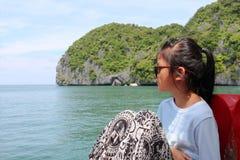 亚裔女孩坐一条小船有海岛的自然视图 库存照片