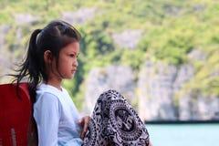 亚裔女孩坐一条小船有海洋的自然视图 免版税库存图片
