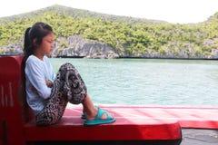 亚裔女孩坐一条小船有海洋的自然视图 库存图片