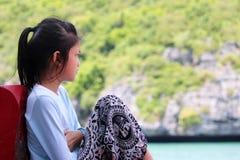 亚裔女孩坐一条小船有海洋的自然视图 免版税库存照片