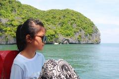 亚裔女孩坐一条小船有海洋的自然视图 图库摄影