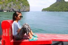 亚裔女孩坐一条小船有海洋的自然视图 免版税图库摄影