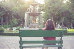 亚裔女孩坐在公园葡萄酒口气s的长凳 免版税库存图片