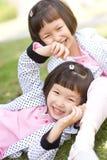 亚裔女孩微笑的孪生 图库摄影