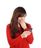 亚裔女孩怀疑地有手机的 免版税库存图片