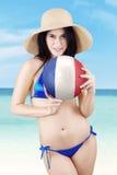 亚裔女孩拿着一个球在海滩 库存图片