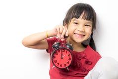 亚裔女孩拿着计数在午餐时间的一个闹钟 免版税库存图片