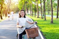 亚裔女孩是微笑和看在自行车的照相机在室外公园,愉快的逗人喜爱的孩子画象有自行车的, 库存照片