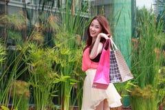 亚裔女孩是愉快购物。 免版税库存图片