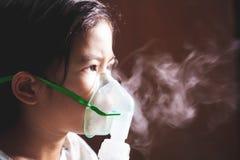 亚裔女孩有哮喘或肺炎疾病和需要nebulization通过在她的面孔的吸入器面具 库存图片