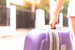 亚裔女孩有拿着回来的大紫色袋子从旅行 免版税库存照片