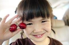 亚裔女孩用樱桃 免版税库存图片