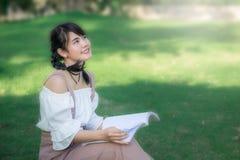 亚裔女孩的开会在公园和读书在 免版税库存图片