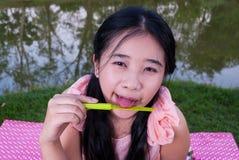 亚裔女孩舔在塑料刀子的果酱 免版税库存图片