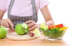 亚裔女孩运载一把刀子,切了苹果对沙拉vegetabl 库存照片