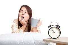 亚裔女孩醒,与闹钟的哈欠和咖啡杯 免版税库存照片