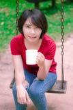 亚裔女孩饮用的咖啡和微笑在庭院里 免版税库存照片