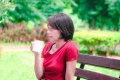 亚裔女孩饮用的咖啡和微笑在庭院里 库存照片