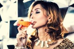 亚裔女孩饮用的鸡尾酒夜总会或酒吧 免版税库存图片