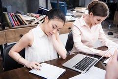 亚裔女实业家与数字式片剂一起使用,当她的工作近在现代办公室时的同事 库存照片
