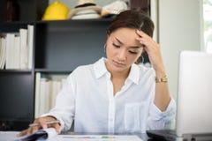 亚裔女实业家严肃对工作被完成直到headac 免版税库存图片