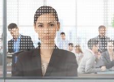 亚裔女实业家在办公室通过窗口 免版税库存照片