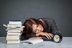 亚裔女实业家得到疲乏的读书许多书 免版税库存照片