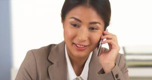 亚裔女实业家谈话在智能手机 免版税库存照片