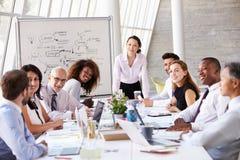 亚裔女实业家主导的会议在会议室表上 免版税库存图片