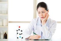 亚裔女性化学家困厄了在剪贴板的化学式 免版税库存图片