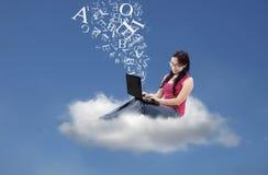 亚裔女性发在云彩的电子邮件 免版税库存照片