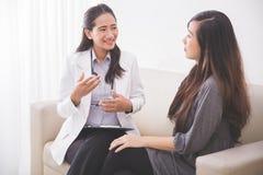 亚裔女性患者与一位女性医生协商 库存照片