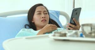 亚裔女性患者使用她的智能手机与朋友谈话和闭上她的眼睛 股票录像