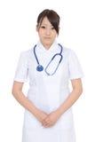 年轻亚裔女性护士用横渡的手 库存照片