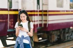 亚裔女性旅客、美丽的妇女使用地图的或社会媒介在智能手机登记在火车站铁路平台 免版税库存照片