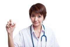 年轻亚裔女性医生写与一个红色标志 免版税图库摄影