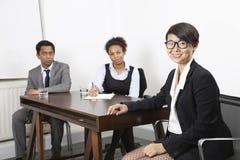 亚裔女性画象有不同种族的同事的在书桌的背景中在办公室 免版税库存图片