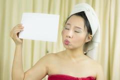 亚裔女服裙子在洗涤头发以后盖她的乳房,包裹在毛巾在举行空的空白的横幅和行动的阵雨以后 免版税库存照片