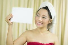 亚裔女服裙子在洗涤头发以后盖她的乳房,包裹在毛巾在举行空的空白的横幅和行动的阵雨以后 库存图片