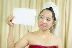 亚裔女服裙子在洗涤头发以后盖她的乳房,包裹在毛巾在举行空的空白的横幅和行动的阵雨以后 图库摄影