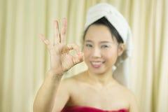 亚裔女服裙子在洗涤头发以后盖她的乳房,包裹在毛巾在阵雨和给姿态标志以后,标志与 库存照片