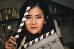 亚裔女演员拿着板岩影片和表现出情感对测试 免版税库存照片