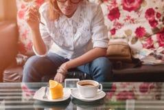 亚裔妇女乐趣吃橙色蛋糕 免版税图库摄影